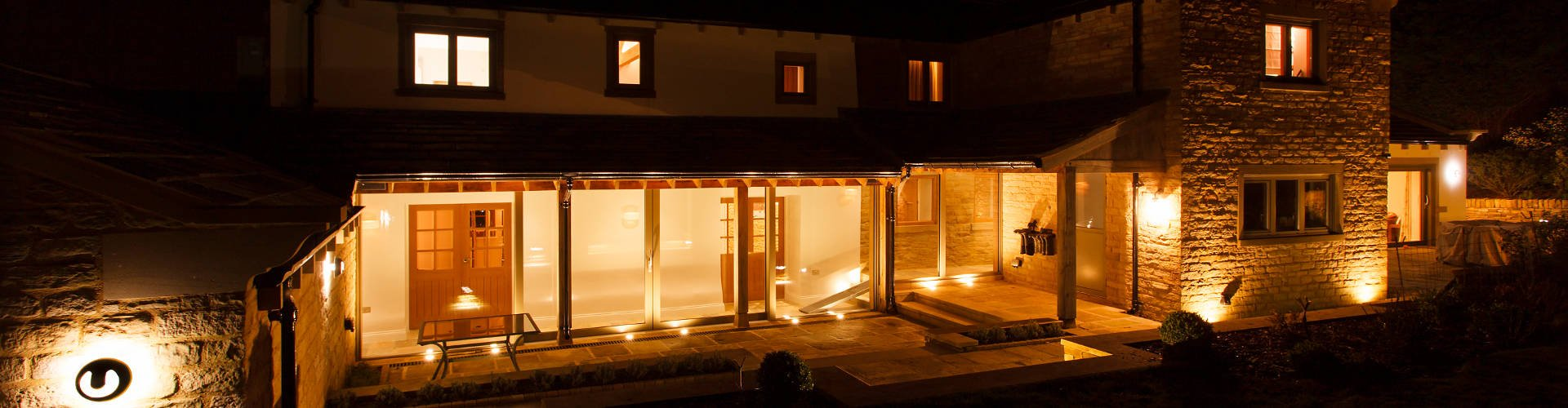 Title Image: A warmly-lit glass hallway linking two ends of a converted Yorkshire farmhouse.